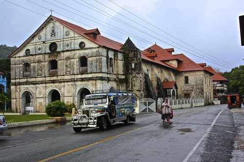 A Jeepney drops off passengers in front of an old building