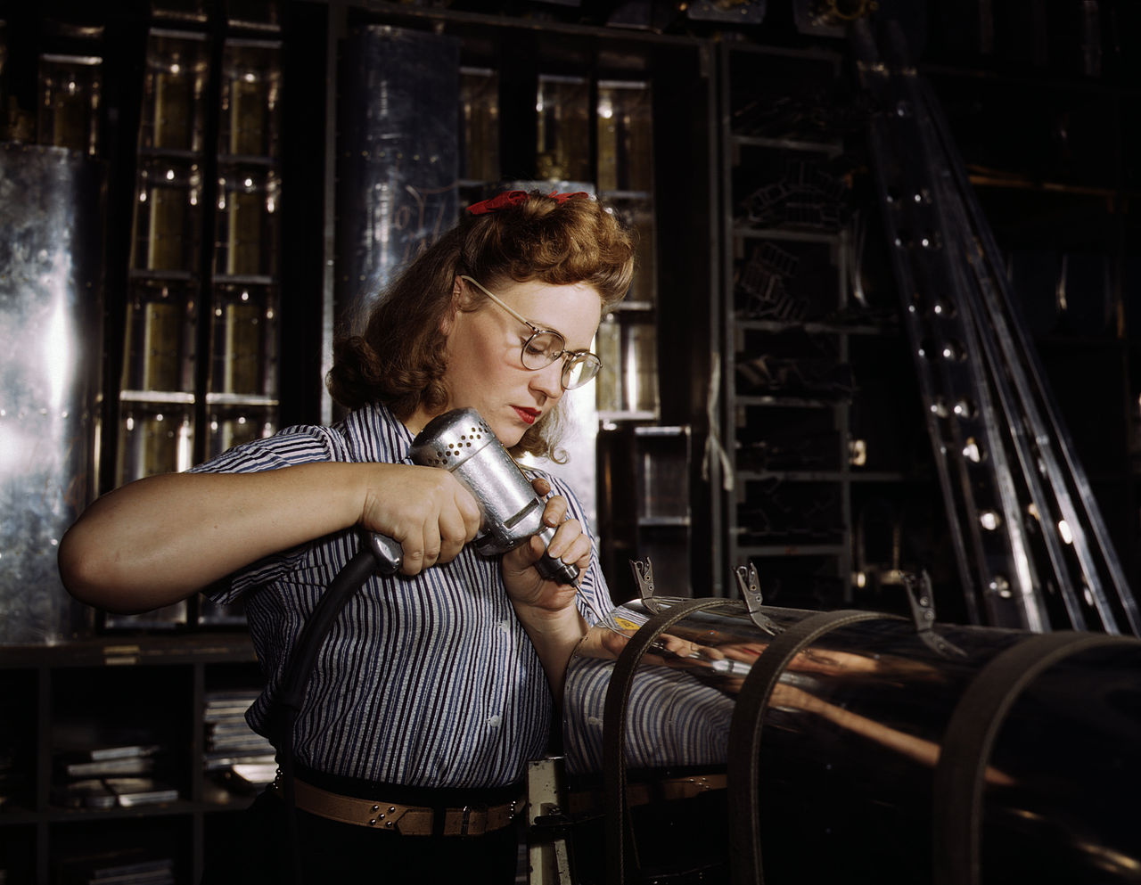 Operating a hand drill at North American Aviation, Inc, a woman is working in the control surface department assembling a section of the leading edge for the horizontal stabilizer of a plane, Inglewood, Calif.