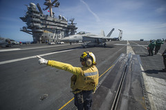 Aviation Boatswain's Mate (Handling) 1st Class Katrina directs an F/A-18E Super Hornet from the Dambusters of Strike Fighter Squadron (VFA) 195 on the flight deck of USS George Washington (CVN 73) as the squadron flies off to return to Atsugi, Japan. (U.S. Navy photo by Mass Communication Specialist 3rd Class Paolo Bayas)