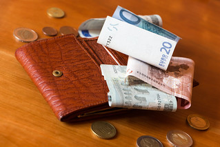 Wallet and some money on a wooden table