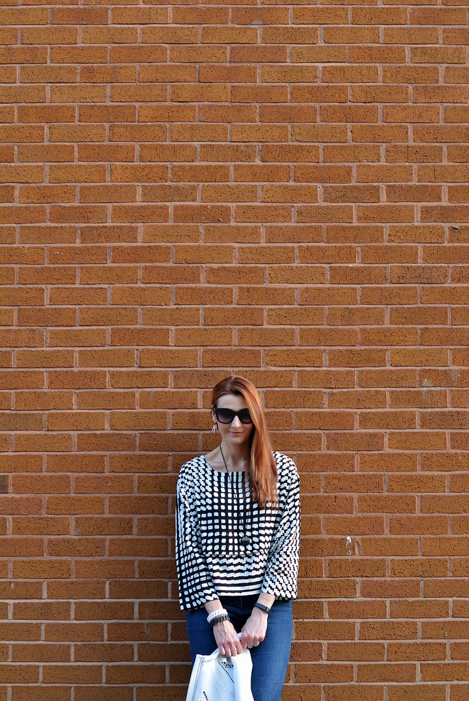 White cut out jacket, black and white graphic boxy top, dark flared denim
