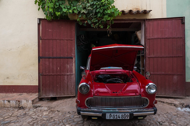 Red Classic car in front of colonial building with vines in Trinidad, Cuba.jpg
