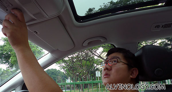 Pressing the electronic button to open up the car roof