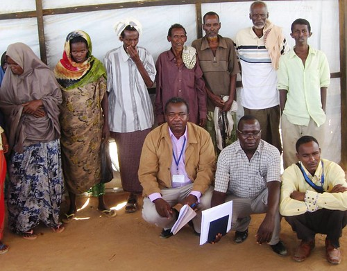 AFSC staff member John Bongei (lower left, in jacket and purple shirt) amongst the beneficiaries of cash relief project in Dadaab refugee camp. Photo: Eric Juma/RRDO