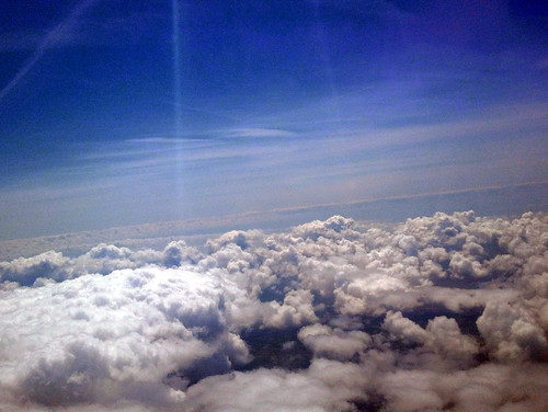 Shot from out the airplane window, flying above the clouds