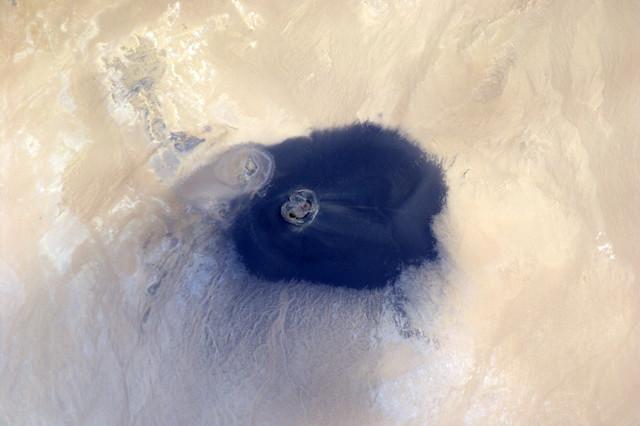 Waw an Namus in Libische Sahara. Afdalend zie je alleen maar zwart vulkaanzand om je heen en waan je je op de maan.