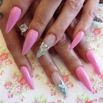 Stiletto nails with pink gel polish and glitter in ring fingers