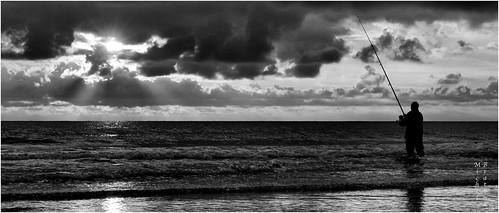 sunset sky bw mer fish france monochrome silhouette les clouds fisherman solitude horizon reflet normandie vagues nuit rayons seul canne pieux crépuscule eos30d canneàpêche pêcheur sylverefexpro2