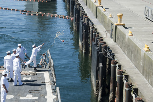 A Sailor aboard USS Ford (FFG 54) tosses a line as the ship pulls into port