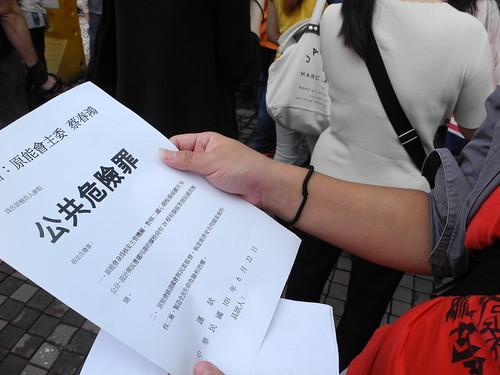 民眾拿著控訴蔡春鴻觸犯公共危險罪的紙張,貼在原能會門前。