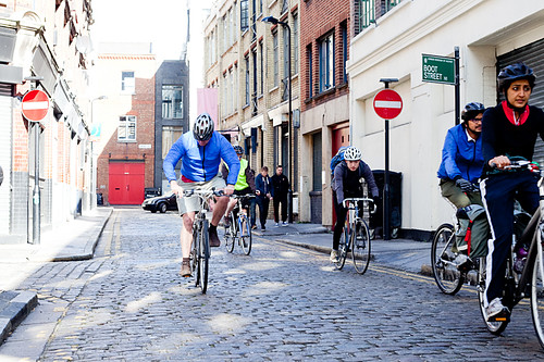 riders on cobbled street