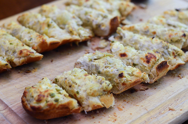 Slices of Cheesy Artichoke Bread on a cutting board.