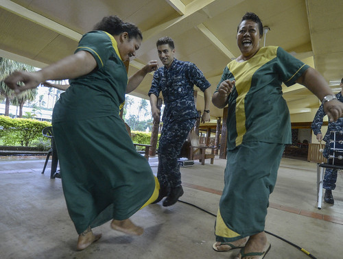 A U.S. Navy Sailor dances with workers of Little Sisters of the Poor nursing home while visiting to donate medical supplies and bedding during Pacific Partnership 2013.