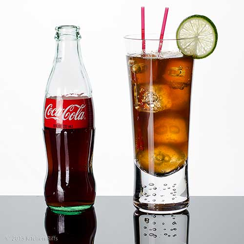 Cuba Libre Cocktail in tall glass with straws and lime garnish, with Coca-Cola bottle