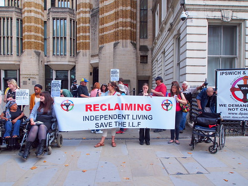 Outside the Department of Health with banner Reclaiming Independent Living Save the ILF