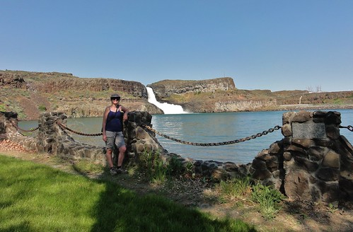 Image shows me leaning against one of the stone pillars anchoring the swooping chain fence, with Summer Falls gushing over the rim of a basalt cliff.