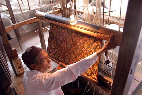 Ein Weber zeigt das Muster seiner Arbeit