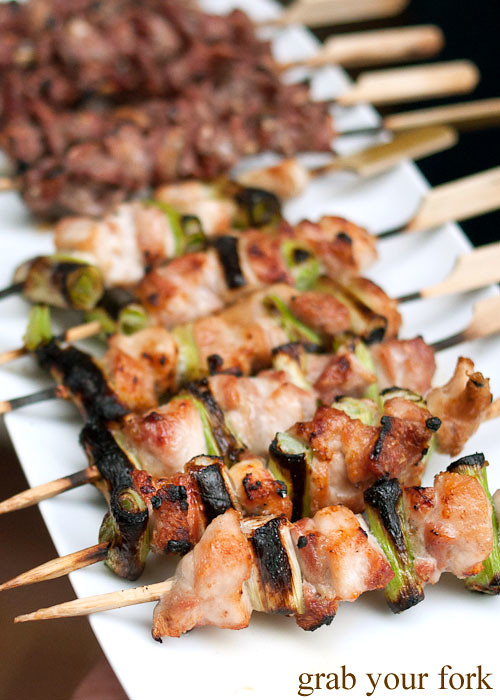 yakitori chicken thigh fillet with leek skewers on an arrosticini charcoal grill at a stomachs eleven japanese dinner