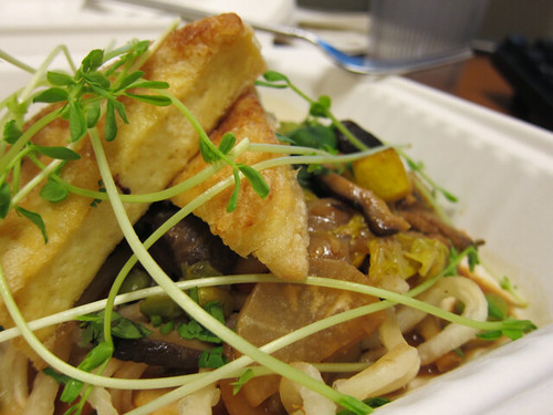 Close-up of an udon noodle and veggie salad topped with triangles of fried tofu.