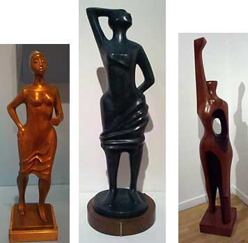 Three statues by Elizabeth Catlett. The first is Stepping Out. It is cast in a bronze-colored material, a minimalist portrayal of a black woman in flowing dress. She has a hand on her hip and an arm in front of her. The second is cast in a black material and is called Standing Strong. It is another black, feminine figure in a dress gathered around her torso. She has one hand her head, one hand behind her back, and strikes a pose that is powerful and dignified. The last sculpture, carved in red cedar, is called Homage to My Black Sisters. It is the most minimalist and abstract out of all the sculptures. It is a recognizable female figure, but the head is not rounded and does not have facial features, and the torso has an oval, concave hole in it. Most notable is the arm raised high above the head in a recognized action of solidarity and pride.
