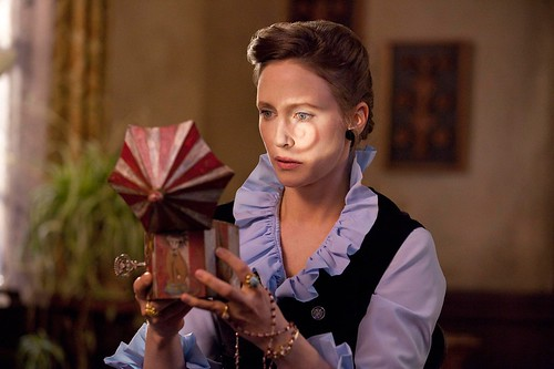 Lili taylor looking at a creepy music box in The Conjuring
