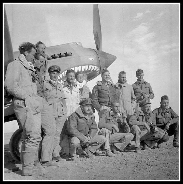 Pilots of No. 112 Squadron RAF grouped round the nose of one of their Curtiss Tomahawks at LG 122, Egypt. - including at 2nd left the famous Neville Duke ( Pilot Officer N F Duke )