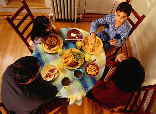 Family of four has dinner together. New USDA report examines the anti-poverty effects of the Supplemental Nutrition Assistance Program (SNAP). Photo: Thinkstock