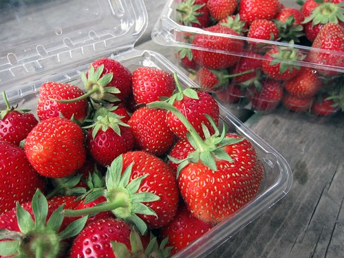 A small container of bright red strawberries in the foreground with a larger container in the background.