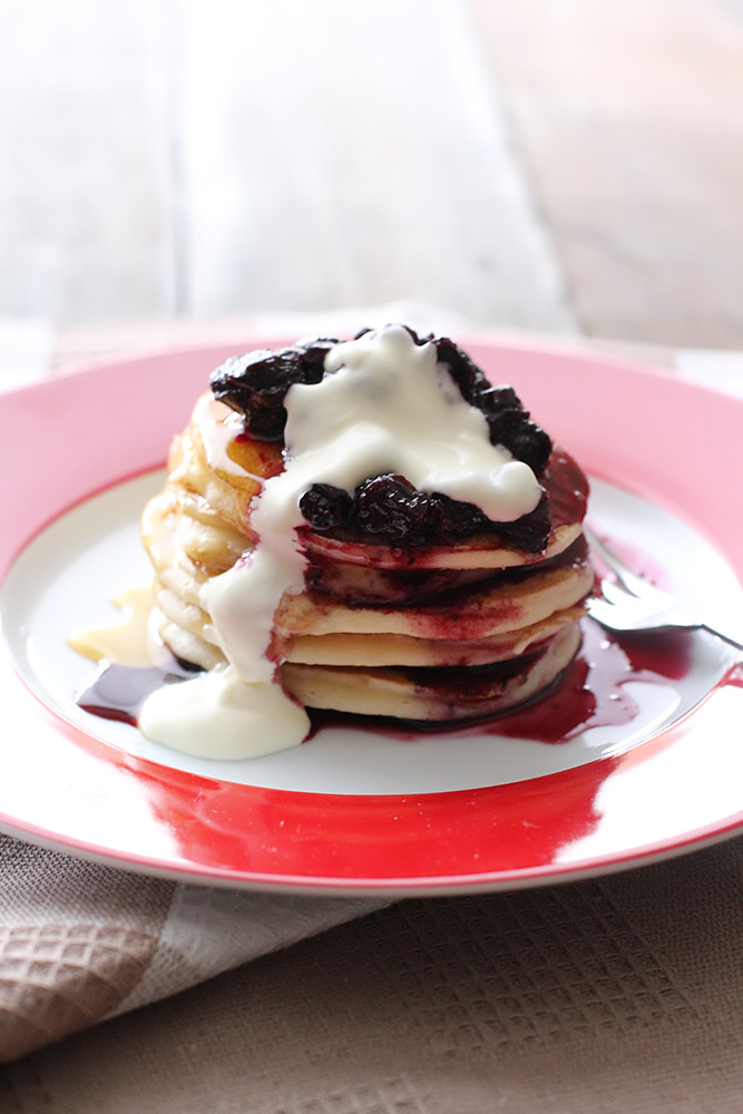 A stack of fluffy ricotta pancakes, served with a blueberry compote and chantilly cream