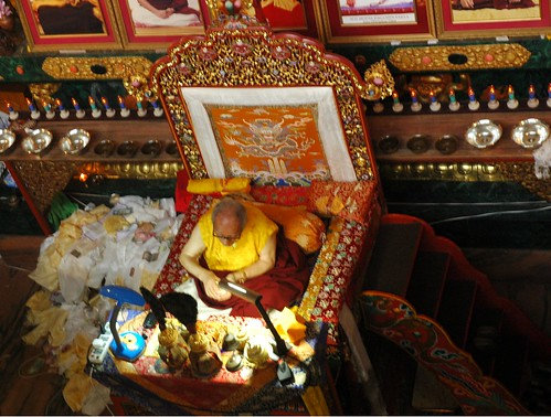 His Holiness Jigdal Dagchen Sakya Rinpoche on his throne with traditional Buddhist impliments, staircase, and a pile of katags mixed with offerings, Sakya Lamdre, Tharlam Monastery of Tibetan Buddhism, Boudha, Kathmandu, Nepal by Wonderlane