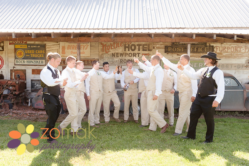 A large party of groomsmen get ready to take a shot before the wedding.
