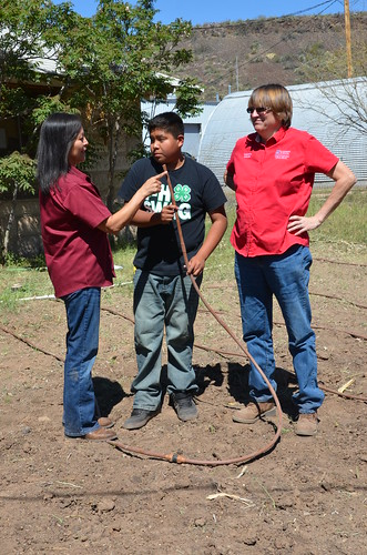 Millie Titla, NRCS district conservationist in San Carlos, Ariz., Noah Titla, San Carlos 4-H Garden Club member, and Sabrina Tuttle, University of Arizona Cooperative Extension tribal extension program agent, inspect the garden's hose, which is used for drip irrigation.