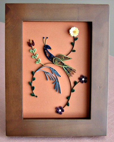 quilled distelfink and floral design in wood frame
