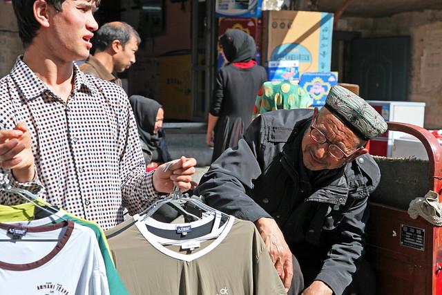 Elderly man looking for clothes in the market, Urumqi ウルムチ、山西巷バザールで服を物色するおじいさん