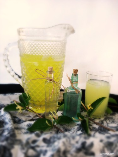 A pitcher of homemade Honeysuckle Lemonade and some honeysuckle floral water gifts