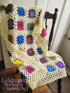 Granny square blanket draped over a wooden chair