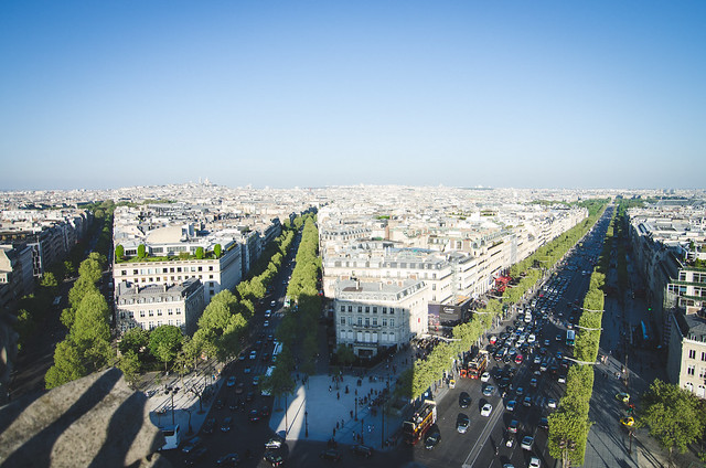 The Arc de Triomphe casts long shadows over the hectic intersection of Champs-Élysées in Paris.