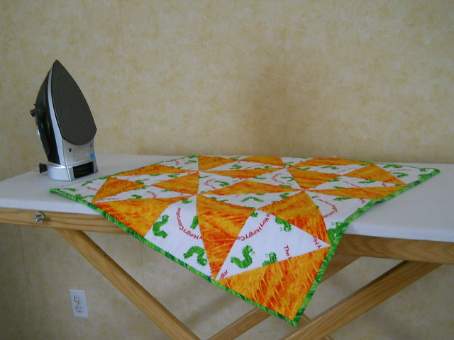 finished baby quilt on ironing board