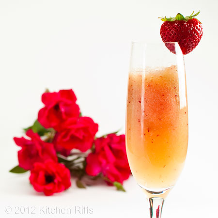 Bellini Cocktail with Strawberry Garnish and Roses in Background, on White