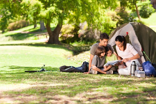 Family of four reading on the grass in front of a tent with tree in background. Photo courtesy of ThinkStock.