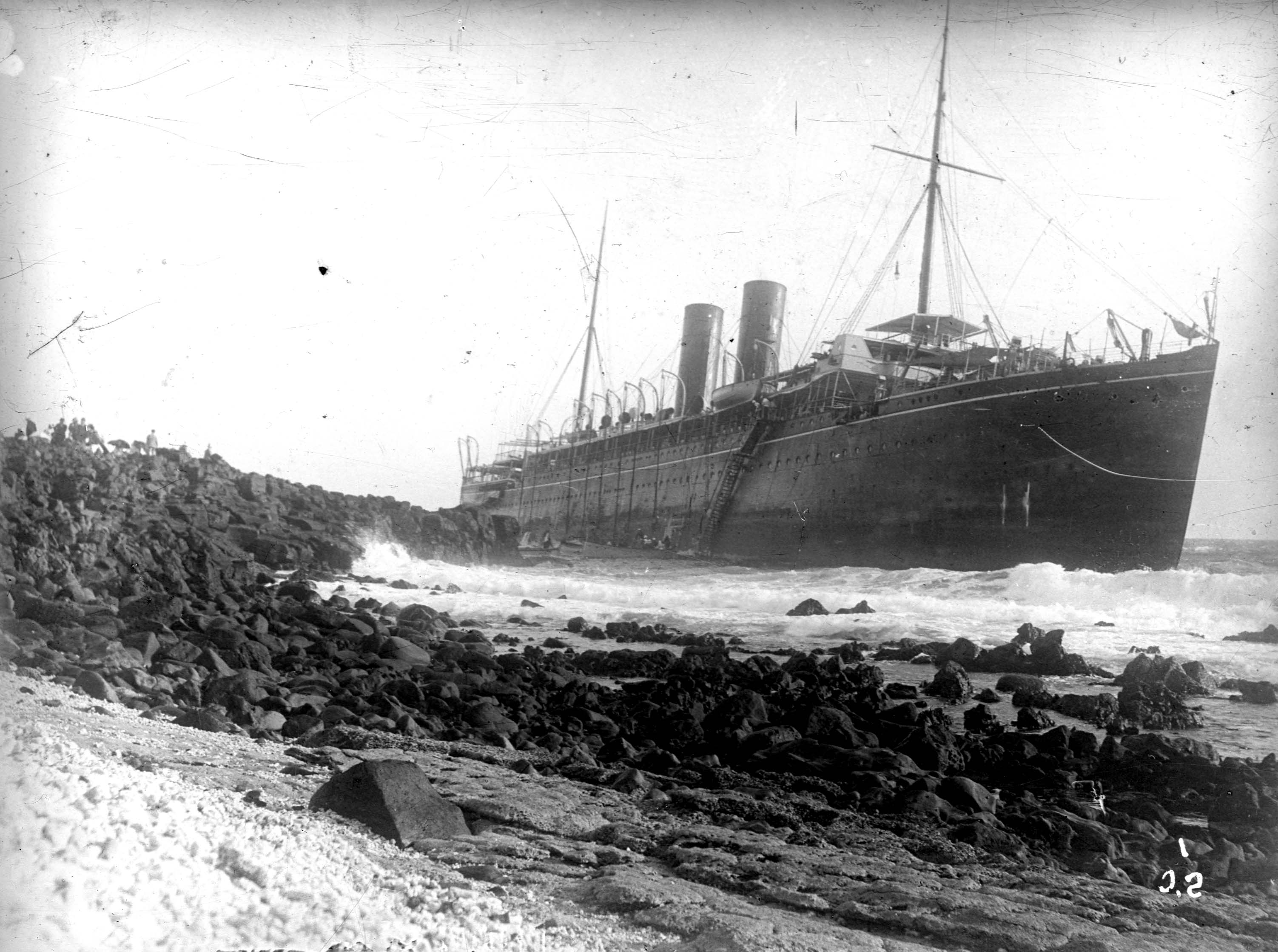 A twin funnel passenger ship aground on a rock covered beach