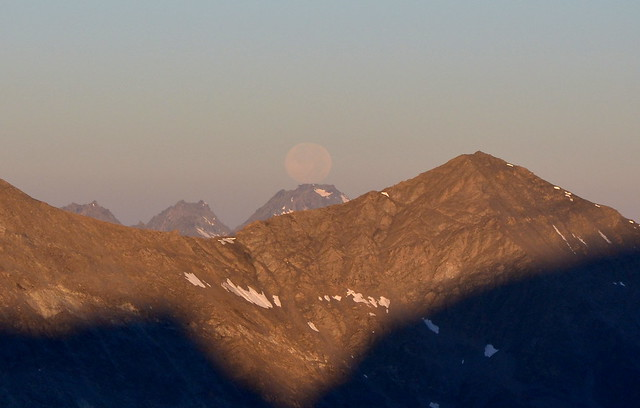 The moon seems to be resting on a mountain top