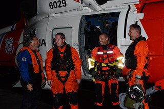 Duane Jones, who was just rescued from his 40-foot sailboat shares a moment with his rescuers upon returning to Coast Guard Air Station Astoria, Ore., Sept. 28, 2013.  An MH-60 Jayhawk helicopter crew from Air Station Astoria rescued Jones who was caught in a fall storm off the Oregon coast.  U.S. Coast Guard photo by Petty Officer 1st Class David Mosley.