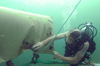 A U.S. Navy diver hooks a lift bag to an object with the help of Trinidad and Tobago divers.