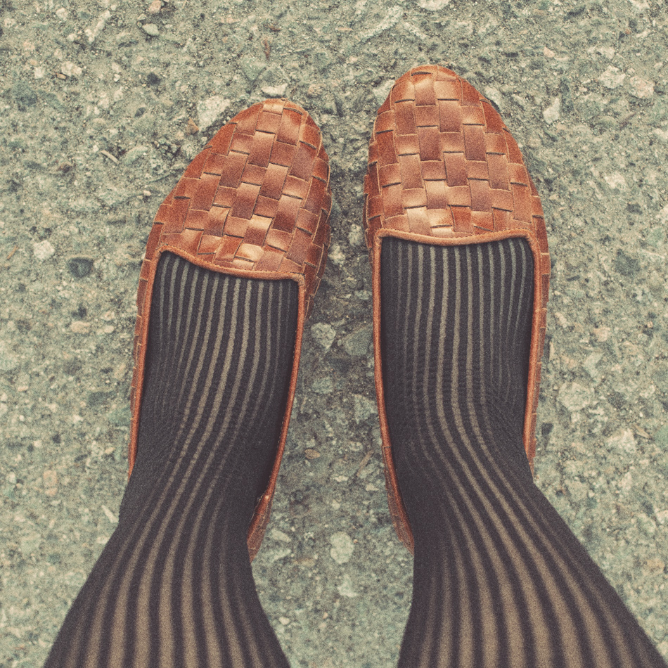 a close up of my feet, showcasing black vertical striped stockings and woven tan leather loafers
