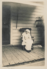 Tiny old woman sits on her rocking chair on the porch