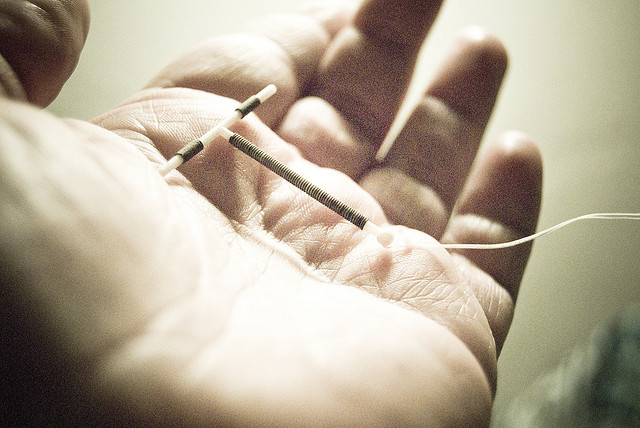A person holds a copper IUD in their hand.