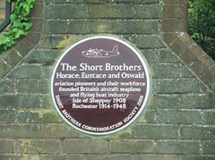 Photo of Horace Short, Eustace Short, Oswald Short, and Short Brothers red plaque