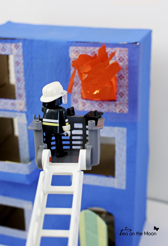 Casa con caja de cartón playmobil y camión bomberos