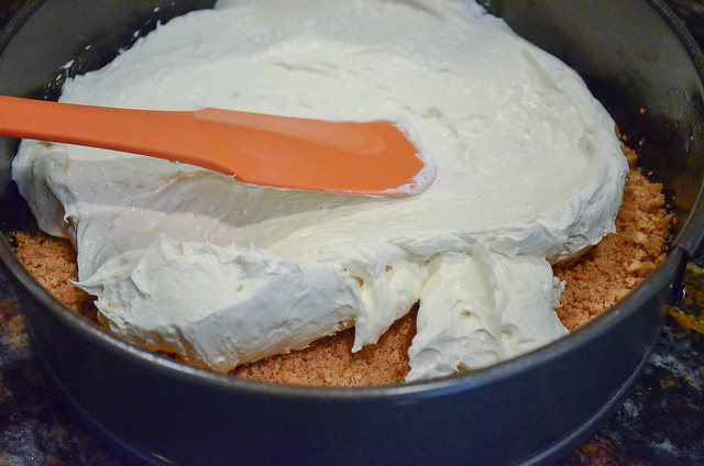 The cream cheese mixture is spread on top of the crumb crust.